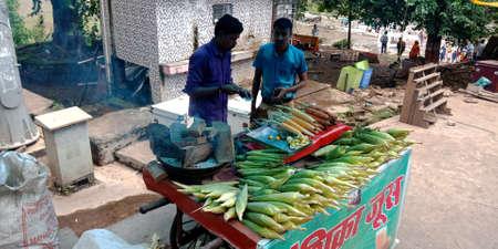 DISTRICT JABALPUR, INDIA - AUGUST 17, 2019: Asian shopkeeper selling sweet corn for tourist at Narmada river street market. Editöryel