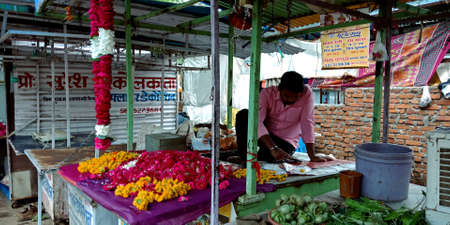 DISTRICT KATNI, INDIA - AUGUST 12, 2019: Asian carriage shopkeeper selling beautiful red rose at indian flower fresh market during hindu holy festival.