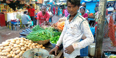 DISTRICT KATNI, INDIA - AUGUST 14, 2019: Asian village poor boy selling veggie at vegetable green fresh market from hand carriage.