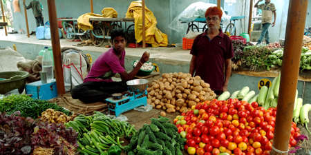DISTRICT KATNI, INDIA - AUGUST 14, 2019: Asian village little boy giving veggie to customer at indian vegetable green fresh agriculture produce market.