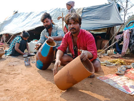 DISTRICT KATNI, INDIA - JANUARY 21, 2020: Indian poor villager artist creating musical drum base on soil field at open area workshop.
