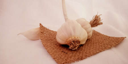 Fresh white color isolated double garlic with set mixed for marketing promotion purpose on brown sack mat surface presentation.