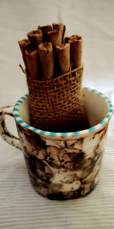 Cup of indian Bidi form of cigarette on brown sack mat background, pack of cigarettes, close-up of a cigarette