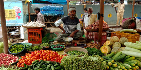 DISTRICT KATNI, INDIA - AUGUST 14, 2019: Asian village vender selling greengrocery at indian vegetable green fresh agriculture produce market.