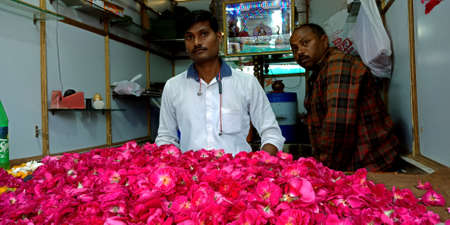 DISTRICT KATNI, INDIA - AUGUST 12, 2019: Asian poor Gardener selling beautiful red rose at indian flower fresh market during hindu holy festival.