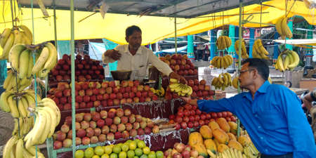 DISTRICT KATNI, INDIA - SEPTEMBER 04, 2019: Indian male fruit vender presenting multiple fruits at local street shop at asian agriculture produce goods market.