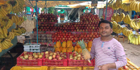 DISTRICT KATNI, INDIA - SEPTEMBER 04, 2019: Indian fruit seller holded pineapple at local street carriage shop at asian agriculture produce goods market.