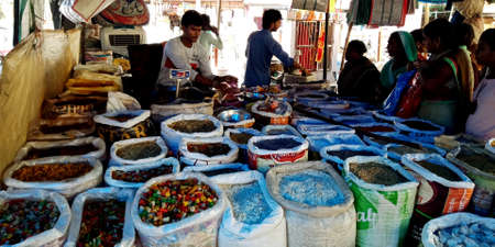 DISTRICT KATNI, INDIA - SEPTEMBER 04, 2019: Indian vender selling hot spice at local street shop at asian agriculture produce goods market.