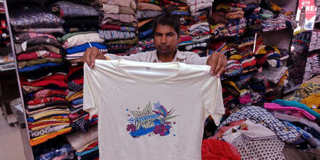 DISTRICT KATNI, INDIA - SEPTEMBER 18, 2019: An indian salesmen selling T- shirt at garment store during indian festival market offers sale. Editorial