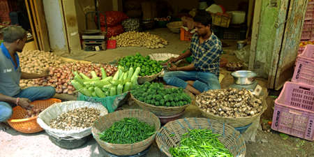 DISTRICT KATNI, INDIA - OCTOBER 13, 2019: An indian village greengrocer selling fresh agriculture goods at vegetable market in asian street.