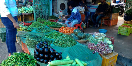 DISTRICT KATNI, INDIA - OCTOBER 13, 2019: An indian village greengrocer selling fresh greens at vegetable market in asian street.