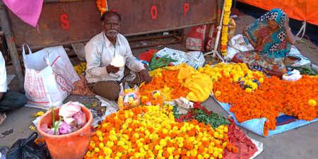 DISTRICT KATNI, INDIA - SEPTEMBER 24, 2019: An indian salesman presenting marigold flowers garland at local shop in asian bazaar. Editöryel