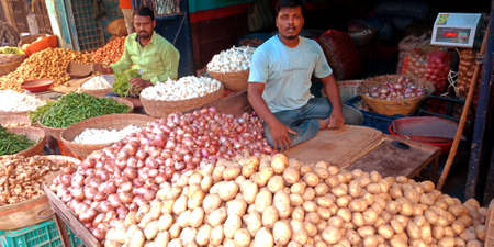 DISTRICT KATNI, INDIA - OCTOBER 13, 2019: An indian village greengrocer selling fresh potatoes and onions at vegetable market in asian street.
