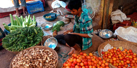 DISTRICT KATNI, INDIA - OCTOBER 13, 2019: An indian village small boy selling fresh agriculture goods at vegetable market in asian street.