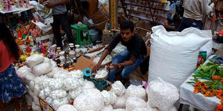 DISTRICT KATNI, INDIA - OCTOBER 19, 2019: Asian poor boy vender selling gods offering for hindu traditional diwali festival, at local street city market.