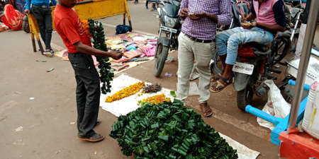 DISTRICT KATNI, INDIA - OCTOBER 19, 2019: Asian male vender selling fresh mango leafs product for worshiping god during hindu traditional diwali festival, at local street city market.