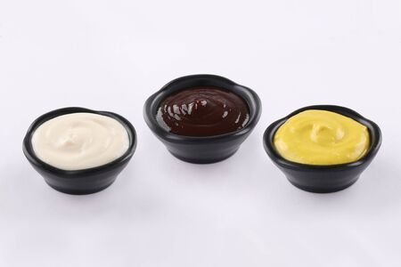 three typs of sauces in black dips, sauce bbq, sauce curry, sauce mayonnaise, on white background