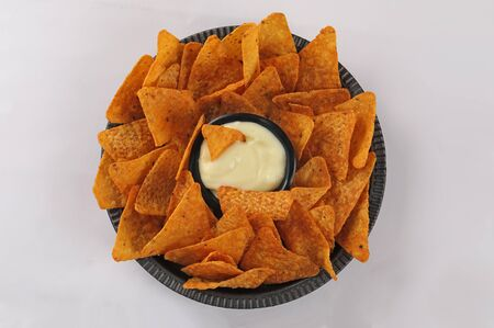 nachos tortilla chips with cheddar sauce and jalapenos top view isolate white background