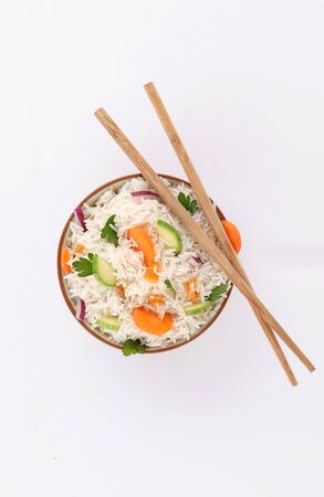 rice bowl with chopstick and parsley and vegetables on white background top view Stock Photo