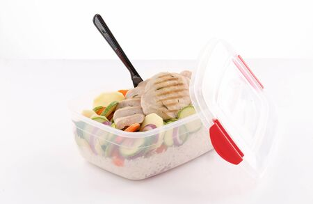 healthy lunch box with grilled chicken breast and steamed vegetables and rice on white background