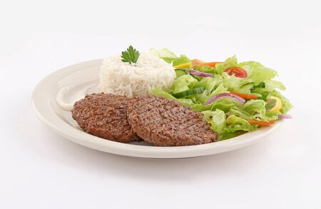 grilled steaks dish with salad and raw vegetables and rice, french fries and sauce on white background Stock Photo