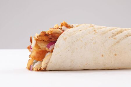 shawerma, shawarma tourtilla wrap with onion, tomato, lettuce and garilc sauce on white background