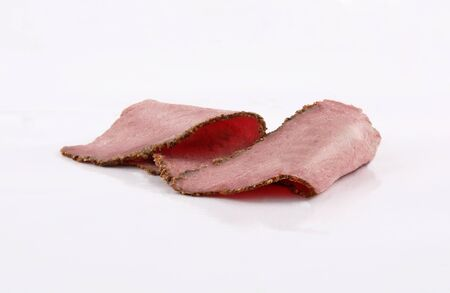 two perfectly arranged slices of roast beef Sliced meat isolated on white background