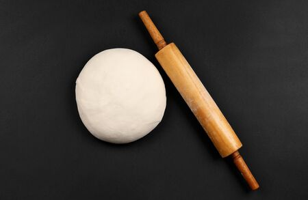 dough and wood rolling pin on clean black background top view Zdjęcie Seryjne