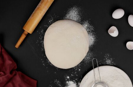 dough and rolling pin and flour, napkin on black background top view Zdjęcie Seryjne