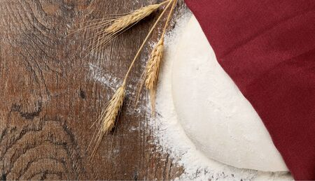 dough under napkin with Wheat ears and Sprinkles of flour on wood background top view