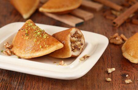 qatayef Ramadan Traditional Sweets walnut jwz  and brown Cinnamon sticks on wood background Zdjęcie Seryjne