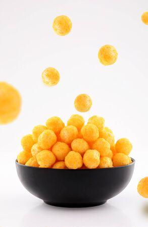 Puffed Ball Käse Maischips in schwarzer Schüssel und bestreut isoliert auf weißem Hintergrund