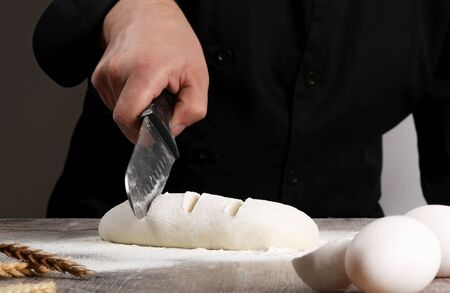 chef cutting dough bugget bread with eggs and ears wheat on wood table Stockfoto