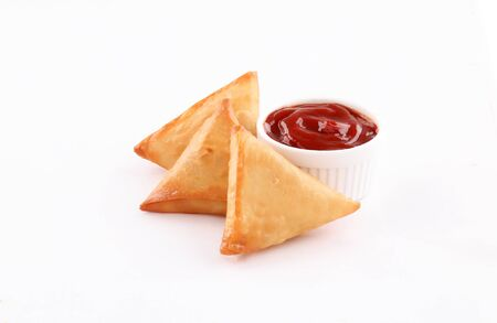 three Pieces golden samosa stuffed with dip red sauce isolated on white background