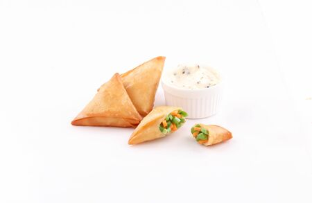 open samosa stuffed vegetables with white dip sause isolated on white background