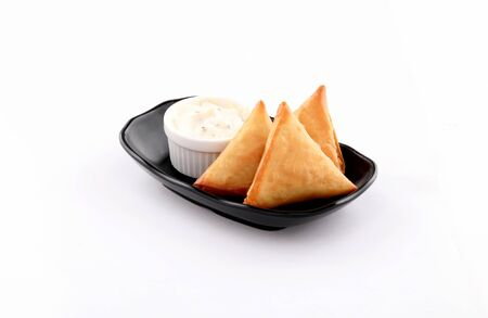 three Pieces golden samosa stuffed in black bowl with dip white sauce isolated on white background