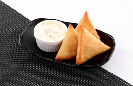 three Pieces golden samosa stuffed in black bowl with dip white sauce on black napkin and white background Stockfoto