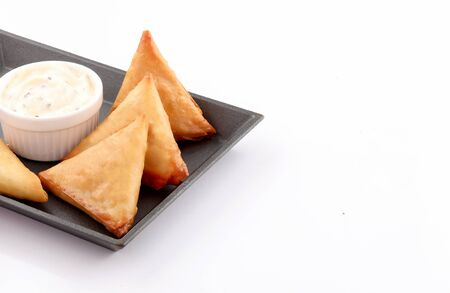 Pieces golden samosa stuffed in black sizzling plate with dip white sauce isolated on white background Stockfoto