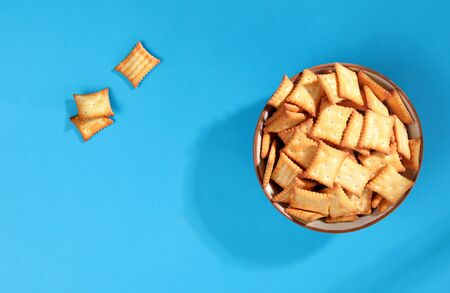 salted biscuit crackers snacks in bowl on blue background top view