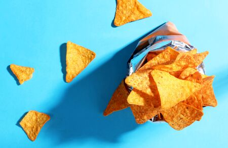 Bag chips doritos pattern top view on blue background