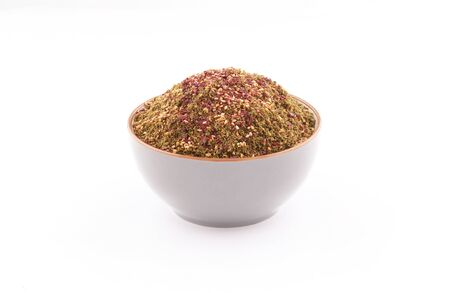 organic zaatar with toasted sesame mIddle eastern spices in a bowl isolated on white background