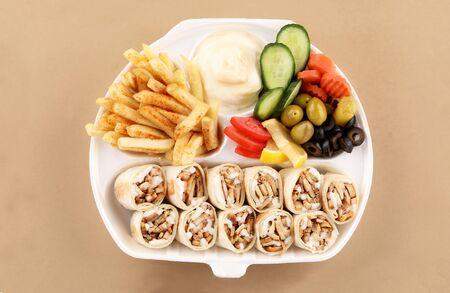 Comida de shawarma dos sándwich de tortilla con aperitivo y patatas fritas en la vista superior de la caja de shawarma