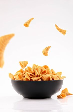 sparse golden cone corn chips in black bowl isolated on white background
