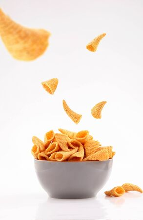 sparse golden cone corn chips in gray bowl isolated on white background