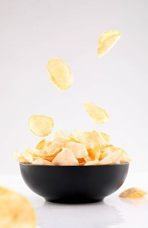 sparse puffed potato chips in gray bowl isolated on white background