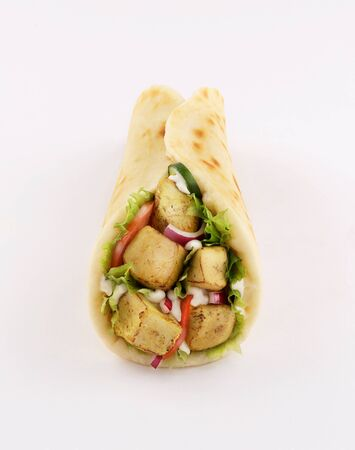 wrap sandwich shish taouk, curry tandoori naan bread with tomato and red onion, front view isolated on white background