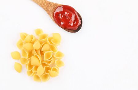 pasta conchiglio with red sauce wooden spoon isolated on white background top view