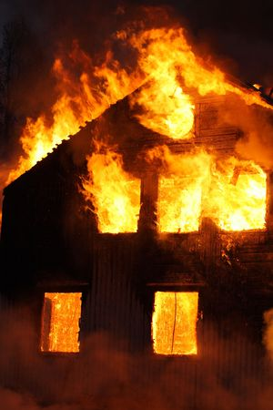 yellow house: An old Wooden house burning Stock Photo