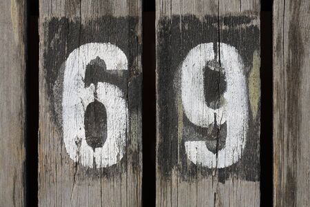 numbering: Gunge painted number 69 on wood. Stock Photo