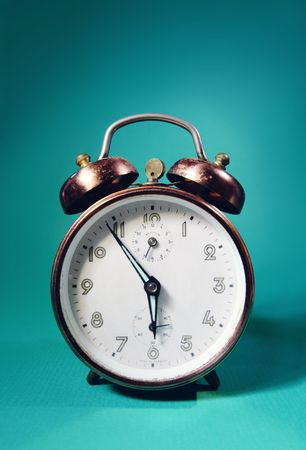 Retro alarm clock on a turquoise background photo